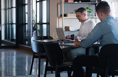 Buy stock photo Shot of two businessmen using their laptops at a desk in a modern office