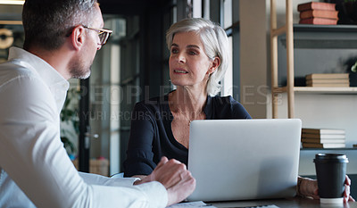 Buy stock photo Shot of a mature businessman and businesswoman using a laptop and having a discussion in a modern office
