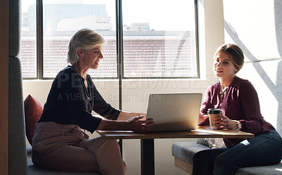 Buy stock photo Shot of two businesswomen using a laptop and having a discussion in a modern office
