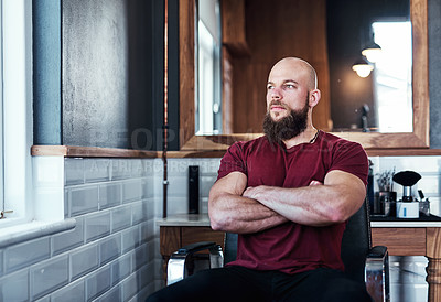 Buy stock photo Cropped shot of a handsome young barber posing with his arms folded inside his barbershop