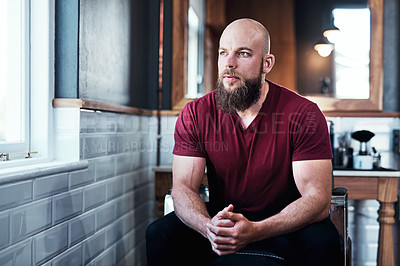 Buy stock photo Cropped shot of handsome young barber sitting on a chair inside his barbershop
