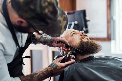 Buy stock photo Cropped shot of a handsome young man getting his beard trimmed and lined up at a barbershop