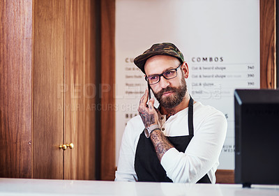 Buy stock photo Cropped shot of a handsome young barber making a phone call inside his barbershop