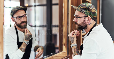 Buy stock photo Shot of a handsome young man looking in the mirror and examining his beard inside a barbershop