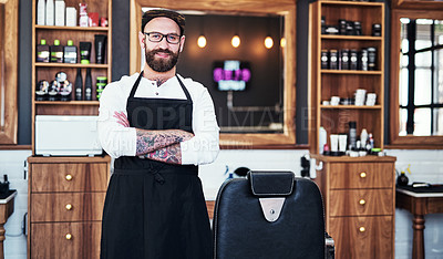 Buy stock photo Portrait of a handsome young barber posing with his arms folded inside a barbershop