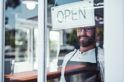 Buy stock photo Cropped shot of a handsome young barber hanging up an open  sign on the window of his barbershop