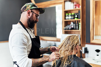Buy stock photo Cropped shot of a handsome male hairdresser styling and treating a woman's hair inside a salon