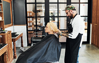 Buy stock photo Cropped shot of an attractive young woman getting her hair styled and treated by a hairdresser at a salon