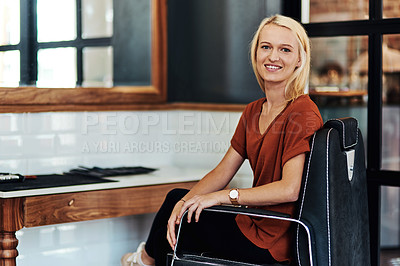Buy stock photo Portrait of an attractive young hair dresser sitting on a chair inside her salon