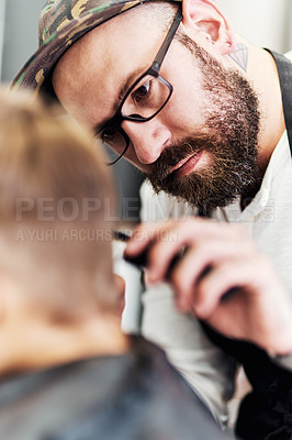 Buy stock photo Cropped shot of a handsome young barber giving a little boy a haircut inside a barbershop