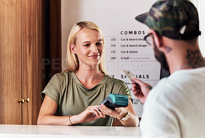 Buy stock photo Cropped shot of an attractive young hairdresser using a credit card machine to action a payment inside her salon