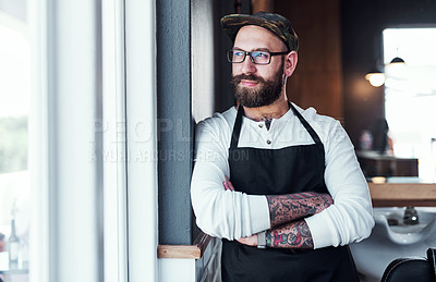 Buy stock photo Cropped shot of a handsome young barber posing with his arms folded inside a barbershop