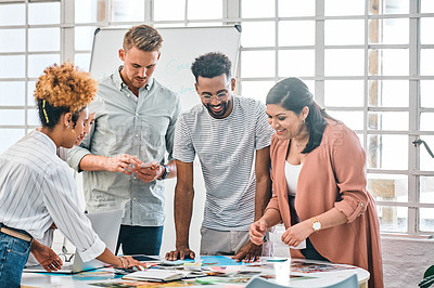 Buy stock photo Cropped shot of a diverse group of businesspeople standing and brainstorming over paperwork together in the office