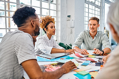 Buy stock photo Cropped shot of a diverse group of businesspeople sitting together and brainstorming over paperwork in the office