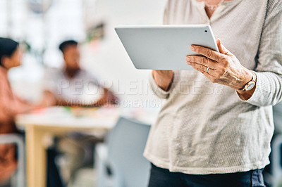 Buy stock photo Cropped shot of an unrecognizable businesswoman standing and using a tablet in the office while her coworkers sit behind her