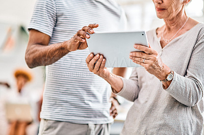 Buy stock photo Cropped shot of two unrecognizable businesspeople standing together and using a tablet in the office