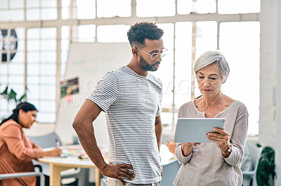 Buy stock photo Cropped shot of two businesspeople standing together and using a tablet in the office