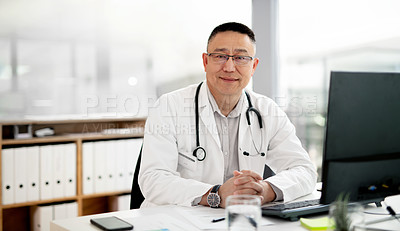 Buy stock photo Portrait of a mature doctor working on a computer inside his office at the hospital
