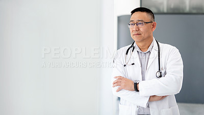 Buy stock photo Shot of a mature male doctor looking thoughtful while standing near a window at the hospital