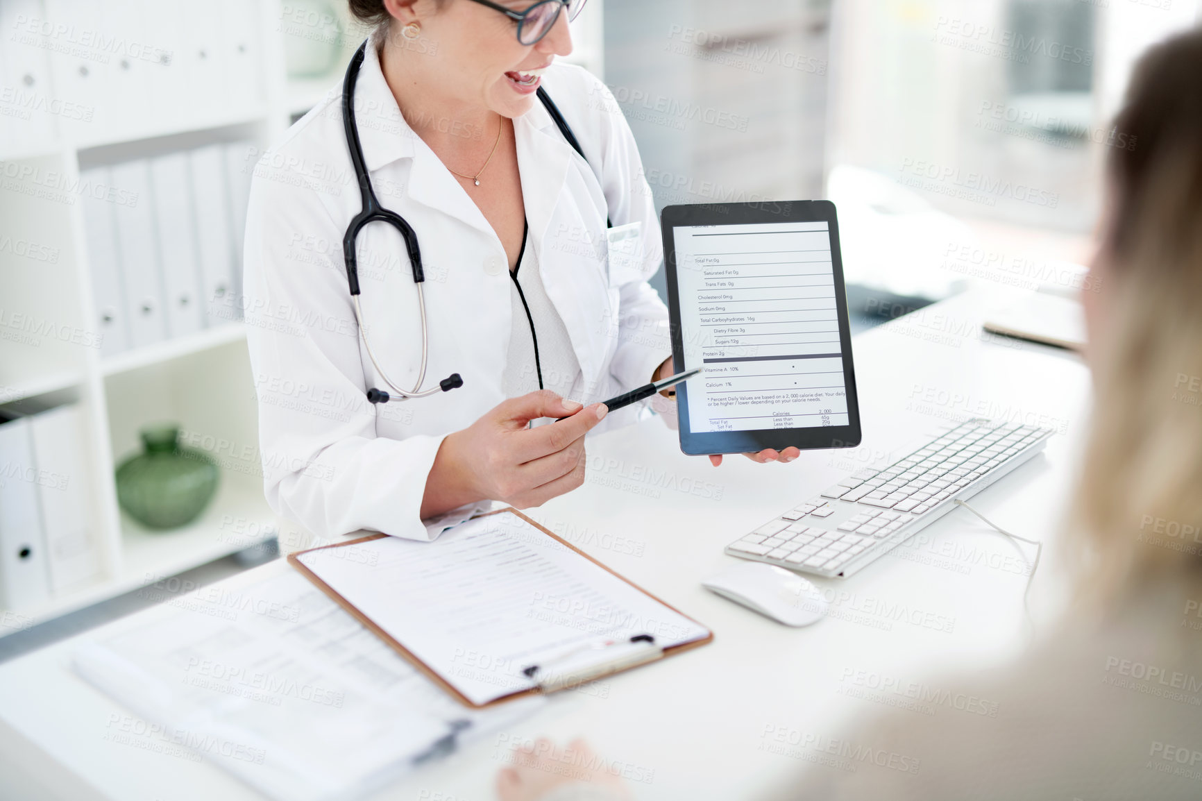 Buy stock photo Cropped shot of an unrecognizable female doctor using a digital tablet while consulting a patient inside her office
