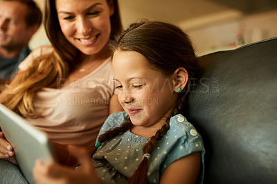 Buy stock photo Shot of an adorable little girl using a digital tablet while relaxing with her family at home