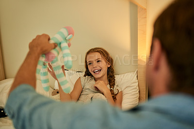 Buy stock photo Shot of a little girl and her father playing with stuffed toys before bedtime at home