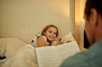 Buy stock photo Shot of a little girl listening to her father read her a bedtime story at home