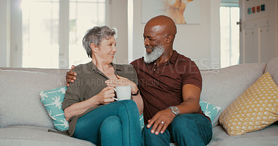 Buy stock photo Cropped shot of an affectionate senior couple sitting next to each other on their sofa in their living room