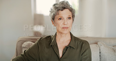 Buy stock photo Cropped shot of a senior woman sitting alone on the sofa in her living room during a day home