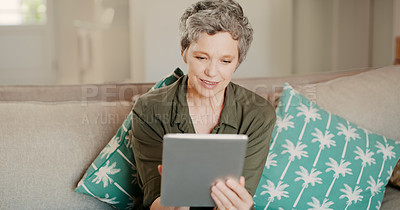 Buy stock photo Cropped shot of a happy senior woman sitting alone on her sofa and using a tablet during a day home