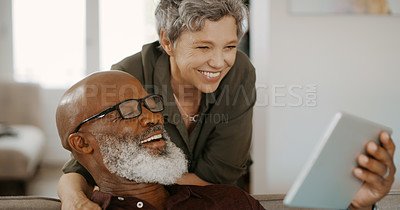Buy stock photo Cropped shot of a happy young couple bonding and using a tablet during a day off in their home