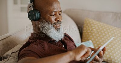 Buy stock photo Cropped shot of a happy senior man sitting alone and listening to music through headphones while using a tablet