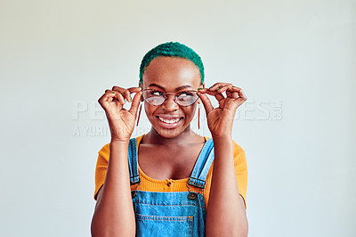 Buy stock photo Shot of a young woman touching her glasses against a white background