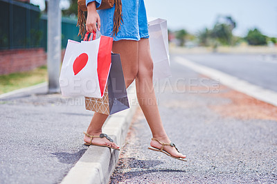 Buy stock photo Cropped shot of an unrecognizable woman crossing the road while holding shopping bags in the city