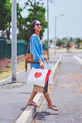 Buy stock photo Cropped shot of an attractive young woman crossing the road while holding shopping bags in the city