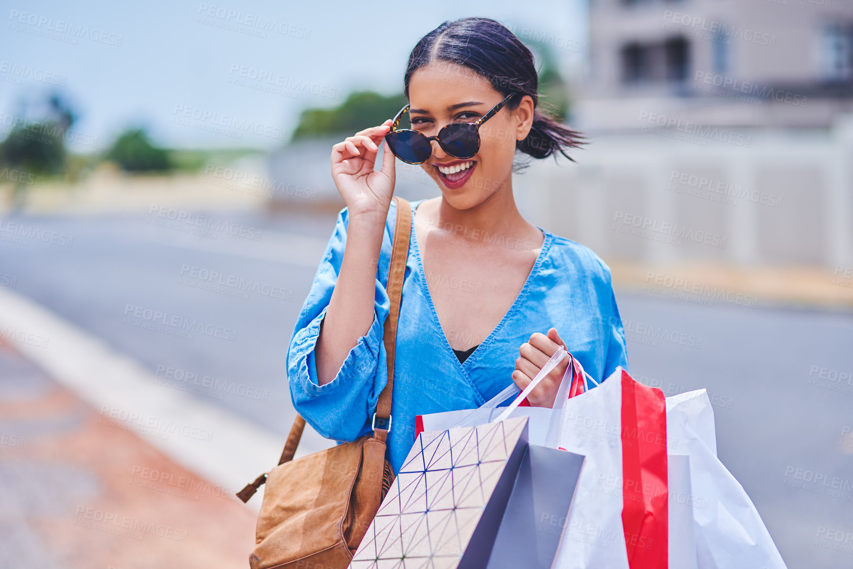 Buy stock photo Cropped portrait of an attractive young woman smiling while holding shopping bags in the city during the day