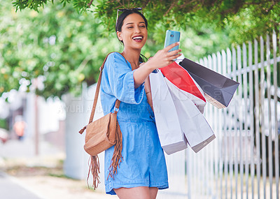 Buy stock photo Cropped shot of an attractive young woman taking a selfie while holding shopping bags in the city during the day