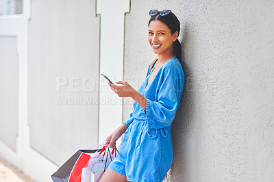 Buy stock photo Cropped portrait of an attractive young woman using a smartphone while holding shopping bags in the city during the day