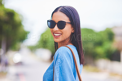 Buy stock photo Cropped portrait of an attractive young woman smiling while standing in the city during the day