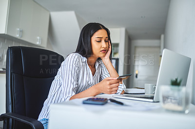 Buy stock photo Cropped shot of an attractive young businesswoman sitting alone and reluctantly using her laptop for online shopping in her home