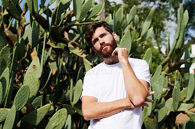 Buy stock photo Cropped shot of a handsome young man posing against succulents outside
