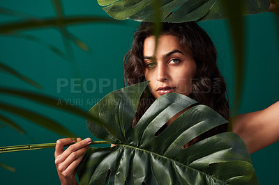 Buy stock photo Cropped shot of a beautiful young woman posing with monstera leaves against a green background