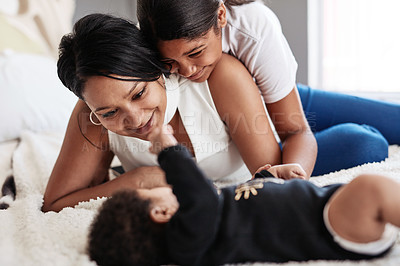 Buy stock photo Cropped shot of a young mother and daughter playing with their baby at home