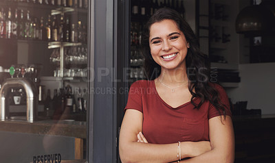 Buy stock photo Portrait of a beautiful young woman standing with her arms crossed in the doorway of her coffee shop