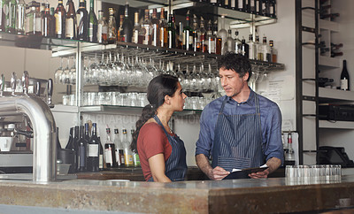 Buy stock photo Shot of two coworkers discussing something on a clipboard in the cafe