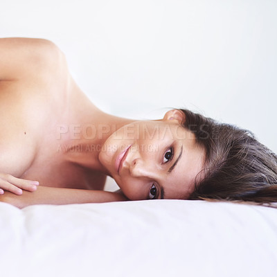 Buy stock photo Cropped portrait of an attractive young woman posing nude on her bed at home
