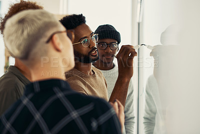 Buy stock photo Shot of a group of businesspeople brainstorming with notes on a glass wall in an office