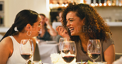 Buy stock photo Cropped shot of two attractive young girlfriends laughing together while dining in a restaurant