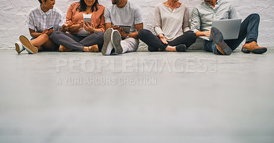 Buy stock photo Shot of a group of businesspeople using their wireless on the floor of a modern office