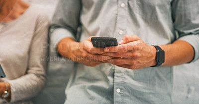 Buy stock photo Cropped shot of a businessman using a smartphone while standing in line in a modern office